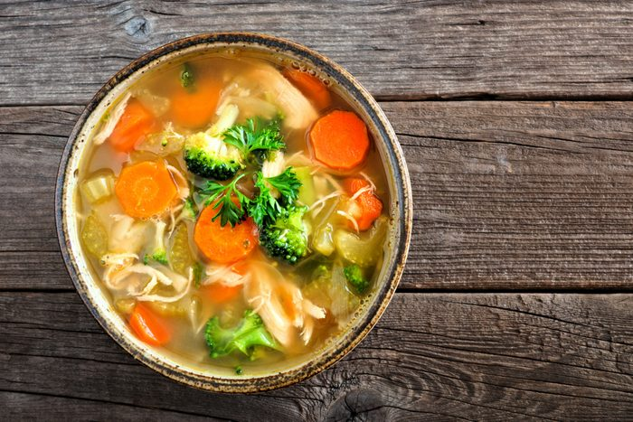 bowl of chicken soup with broccoli and carrots