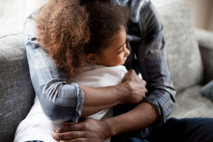 Close up African American family daddy and daughter spend time together at home. Black father embrace sincere little preschool girl sitting on couch. Happy fatherhood loving wellbeing family concept