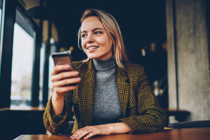 Cheerful blonde female blogger in stylish jacket laughing and looking away while holding smartphone and messaging in chat via free 4G internet connection sitting at wooden table in coworking space