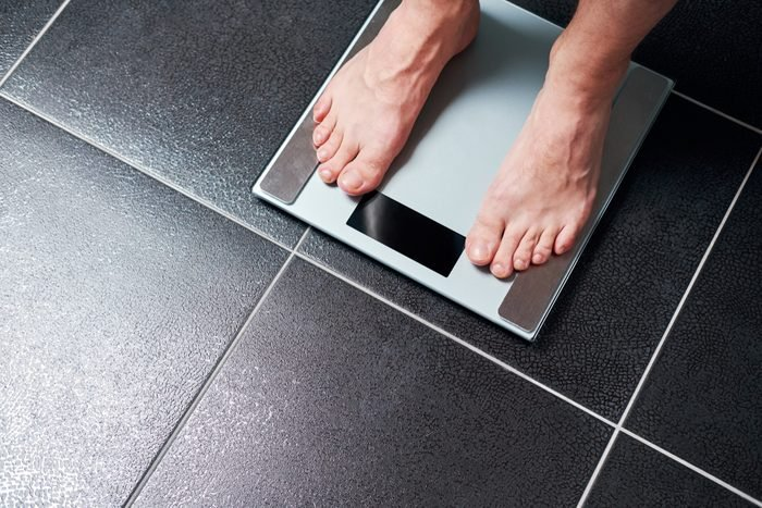 Man on the scale in the bathroom.View of male feet from above.