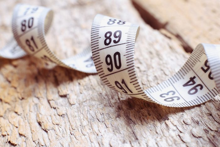 Centimeter on the table. Measuring tape on a table. Diet, weight loss, sports. The concept of slimness. Wellness. Measuring tape on old wooden table.