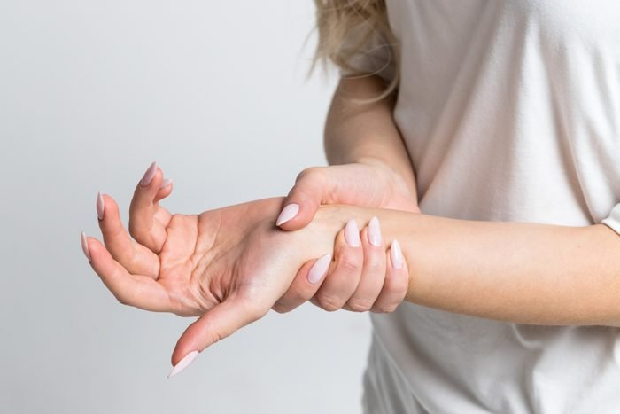 Closeup of female arms holding her painful wrist caused by prolonged work on the computer, laptop.Carpal tunnel syndrome, arthritis, neurological disease concept.Numbness of the hand