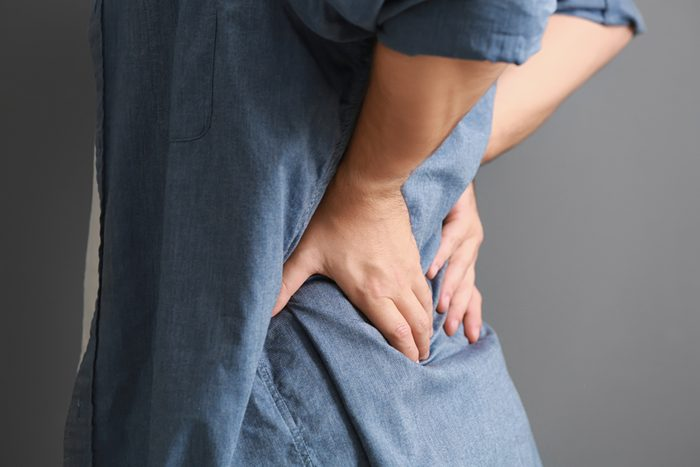 Man suffering from back pain on grey background