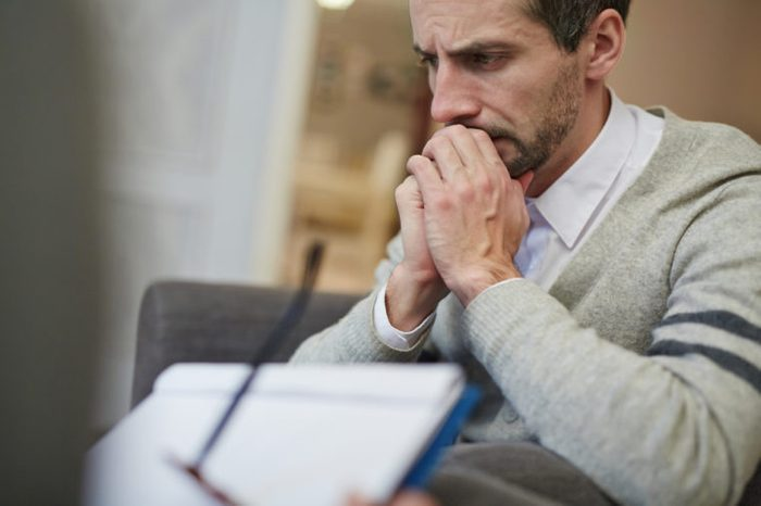 Waist-up portrait of disappointed bearded patient absorbed in thoughts while his psychiatrist filling in medical card
