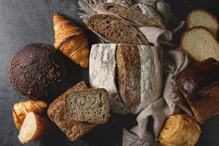 Variety of fresh baked rye, spelled, wheat craft artisan bread, whole and sliced, on cloth over black texture background. Flat lay, space