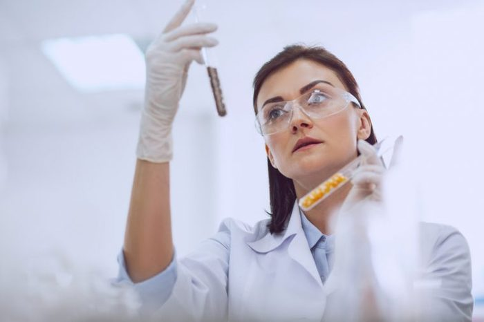 Doing research. Beautiful skilled scientist wearing a uniform and holding seed samples