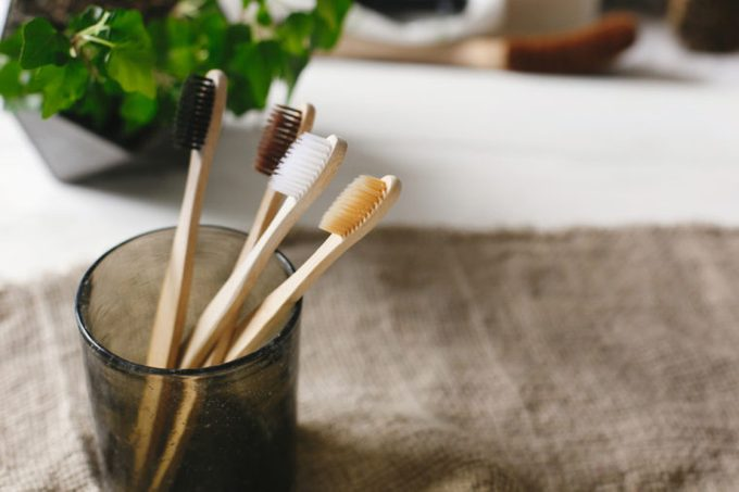 eco natural bamboo toothbrushes in glass on rustic background with greenery. sustainable lifestyle concept. zero waste home. bathroom essentials, plastic free items