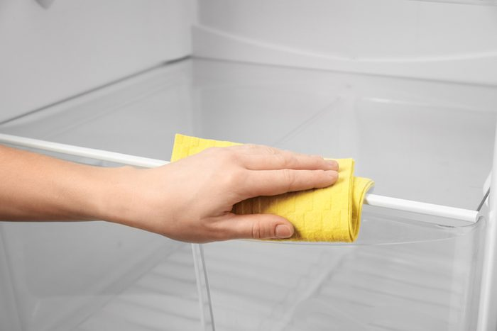 Woman cleaning refrigerator with rag, closeup
