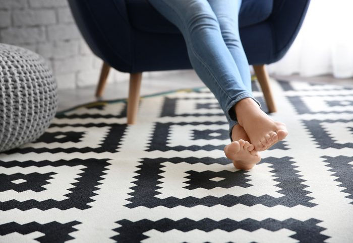 Woman sitting in chair with bare feet on carpet