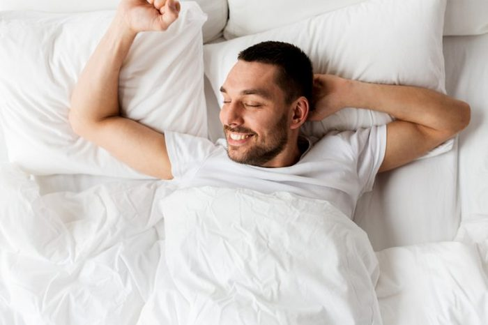 people, bedtime and rest concept - man lying in bed at home