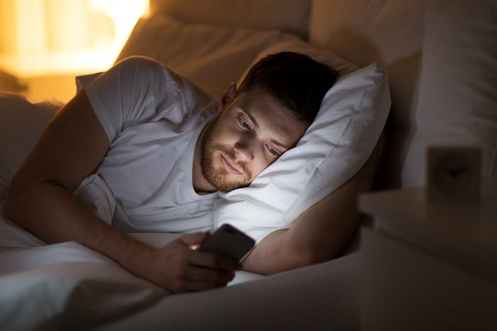 man using phone in bed at night
