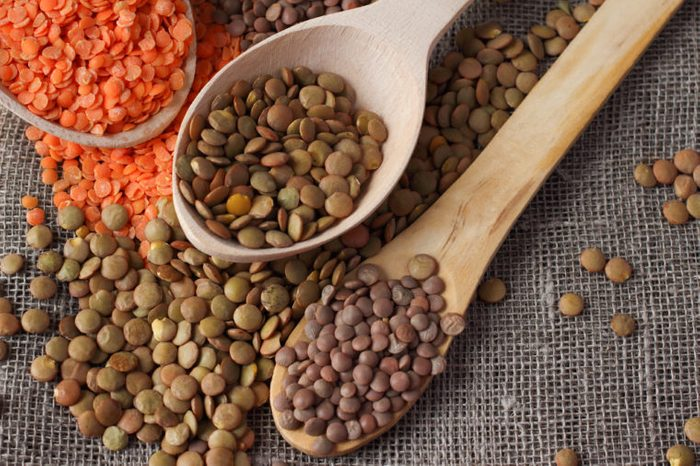 Green and red lentils in wooden spoons on sackcloth