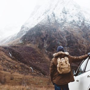 Man driving car on to the mountains. Traveler with backpack. Hiking in cold weather.