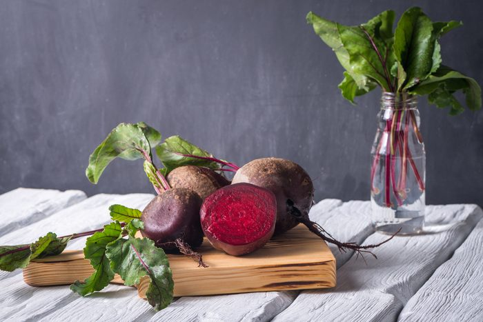 Beetroots on white painted rustic wooden table with slate background.