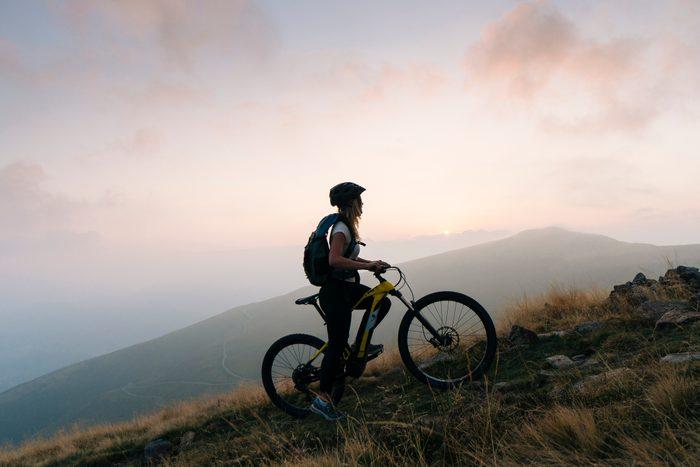 female mountain biker climbing up mountain