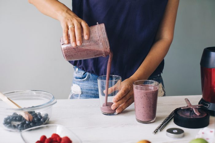 woman pouring fresh fruit smoothie into glass