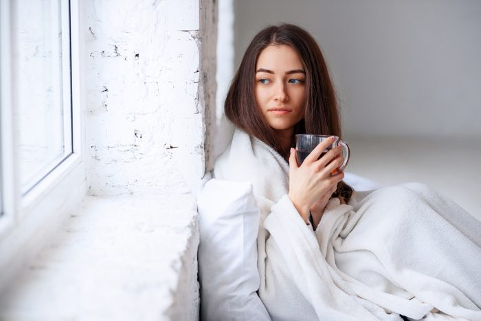 Young woman sipping coffee in bed, looking pensive