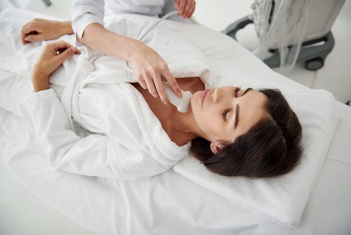 Portrait of beautiful lady in white bathrobe having ultrasound scanning of thyroid