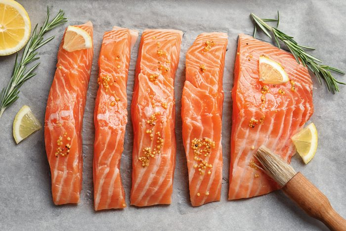 Fresh salmon with mustard on parchment, top view