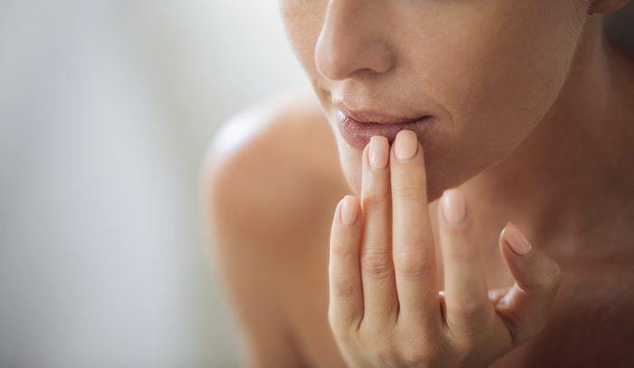 woman touching her lips.