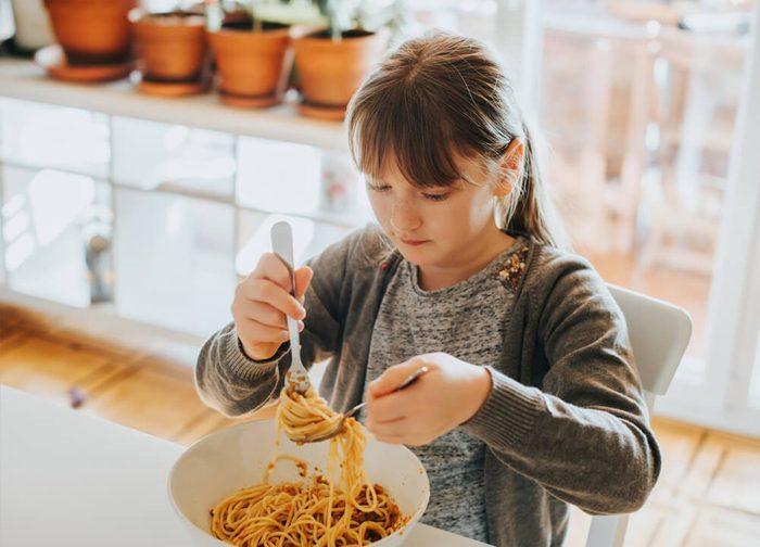 Little kid girl eating spaghetti bolognese at home for lunch