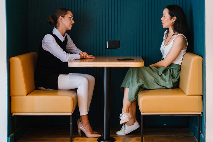 women sitting at table discussing talking