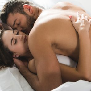 beautiful young couple cuddling in bed in morning
