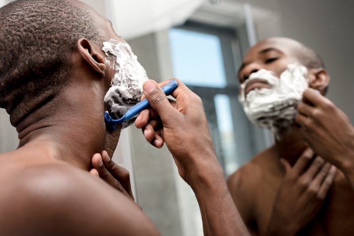 selective focus of handsome african american man shaving and looking at mirror