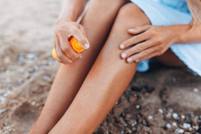 Beautiful girl, sun cream application, on the beach, feet close-up, jar of sun cream