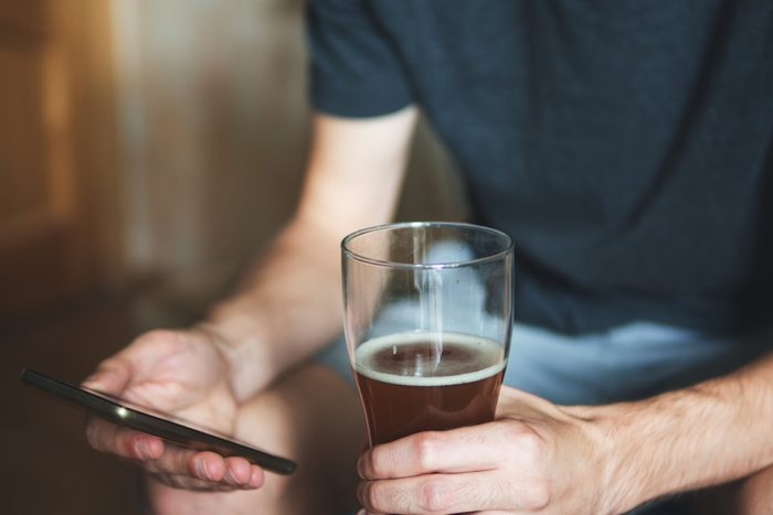 person holding glass of alcohol and phone
