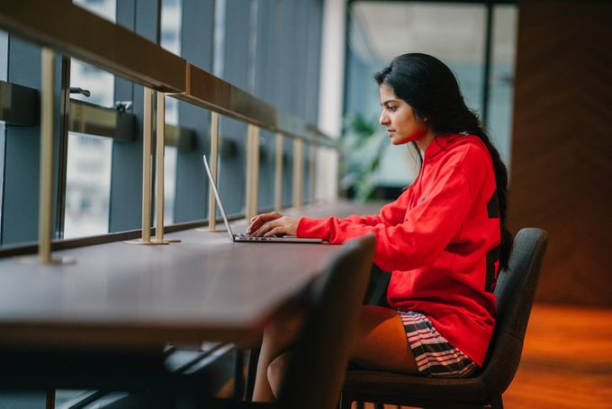 A young and attractive Asian Indian student woman works on her notebook laptop at a wooden desk during the day. She is focused and typing on her notebook; the very image of productivity.
