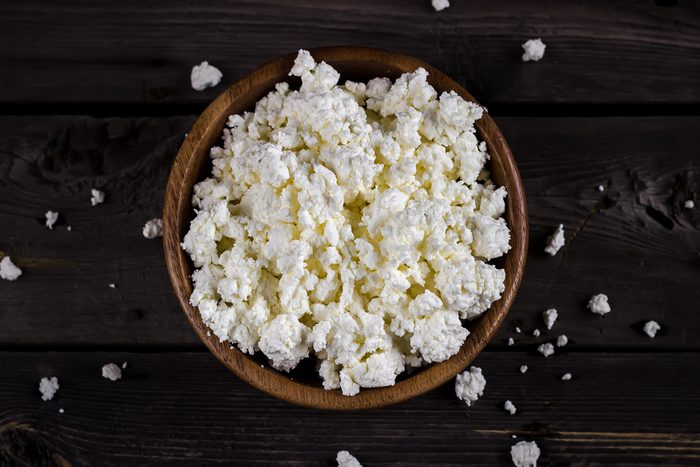 Cottage cheese in a bowl on wooden table. Style rustic. Selective focus.