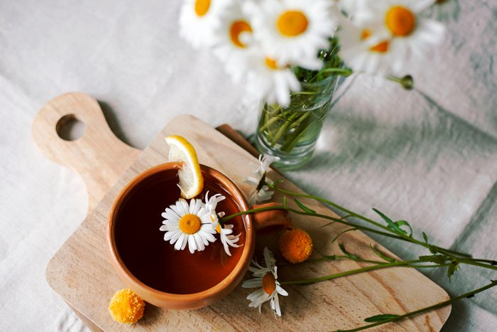 Herbal tea with fresh chamomile flowers in a ceramic mug on a linen tablecloth