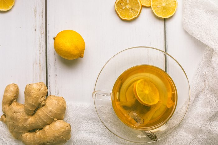 Healthy, organic green tea with sliced ginger and lemon, in a glass cup