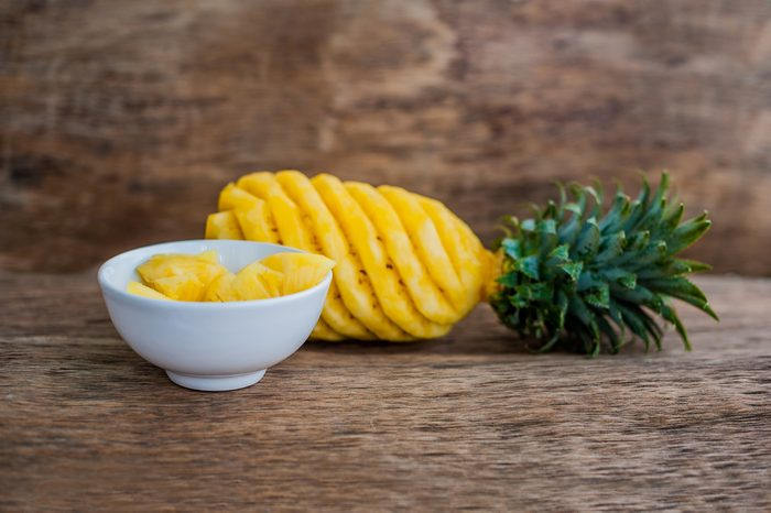 Pineapple slices and pineapple shelled Asian-style on wooden background.
