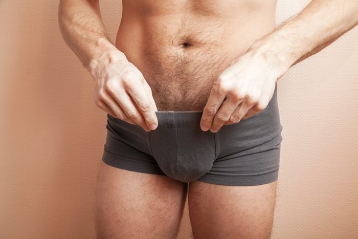 Young adult sporty man pulls out dark gray boxer underpants, close-up studio photo with selective focus