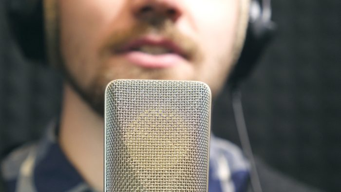 Young man emotionally recording new song. Working of creative musician. Male singer in headphones singing song into the microphone at sound studio. Show business concept. Slow motion Close up.