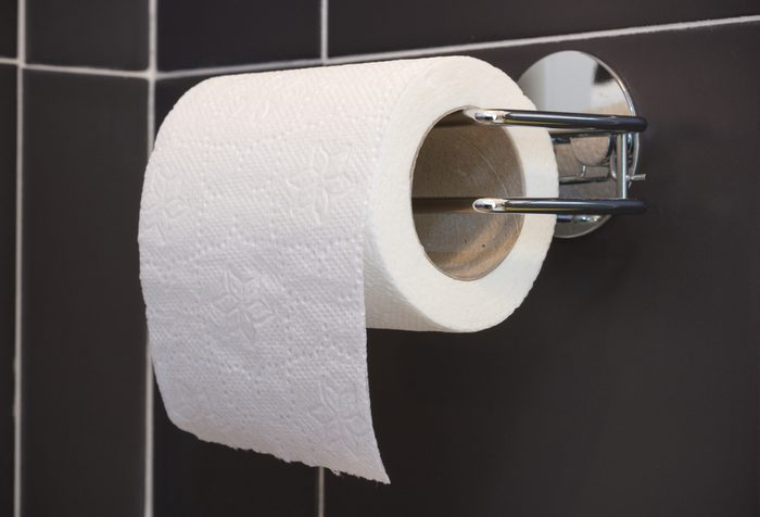 Toilet paper roll and holder on the wall of the bathroom