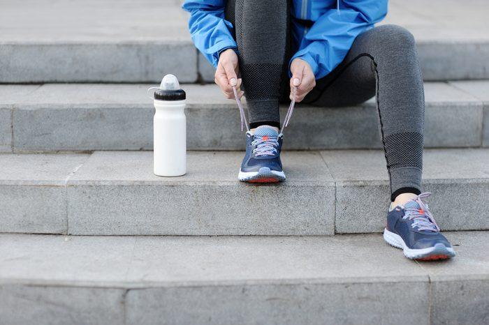 Woman runner tying laces before training. Marathon