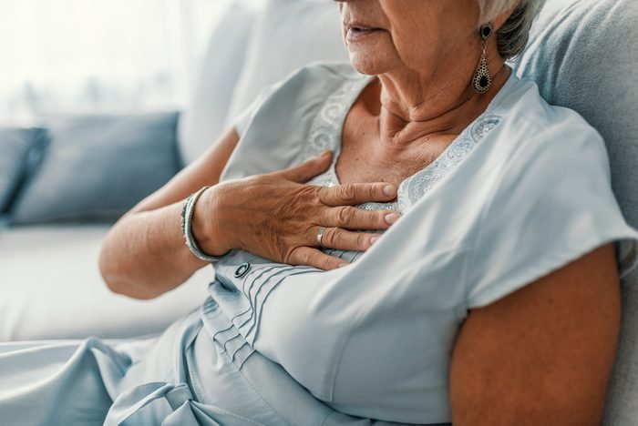 Woman having a pain in the heart area. Heart Attack. Painful Chest. Health Care, Medical Concept. High Resolution. Woman having heart attack at home