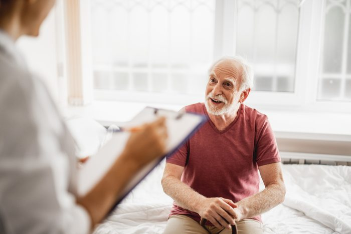 Portrait of bearded gentleman with walking stick discussing his state of health with female physician. He is looking at young lady with smile