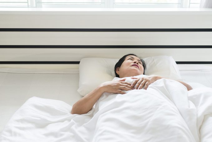 Elderly asian woman depressive have a headache and feeling consider seriously in bedroom