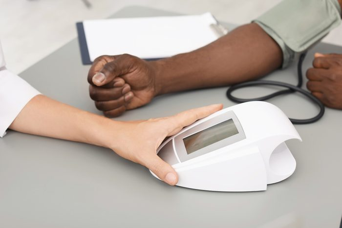 doctor or nurse checking patient's blood pressure