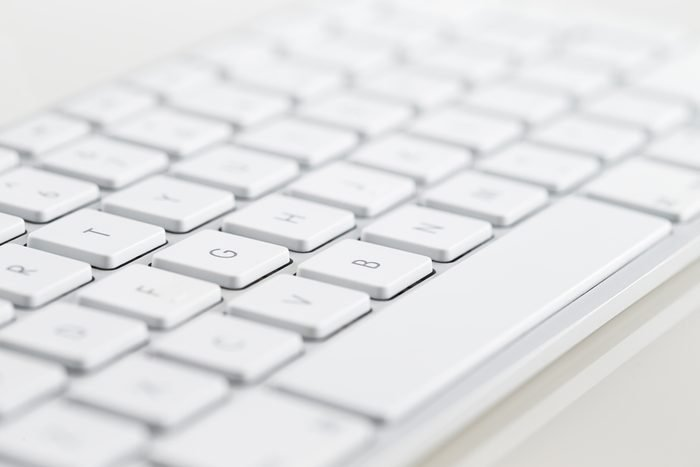 A close-up of a white computer keyboard on a white background
