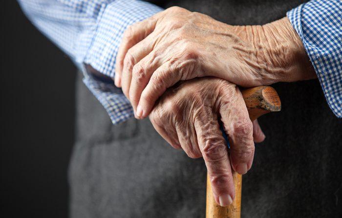 Closeup of senior woman's hands on wooden walking stick