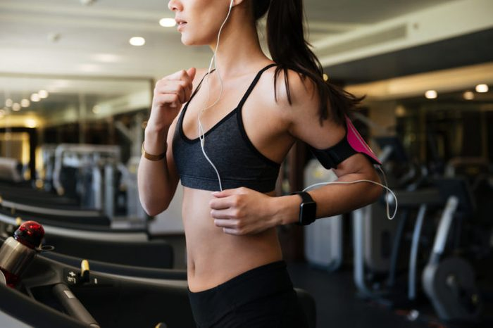Cropped picture of young amazing fitness woman make sport exercises indoors at gym while listening music.