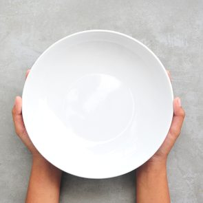 Female hands hold empty dish on stone background.