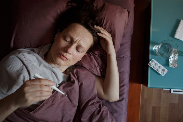 woman laying in bed with fever