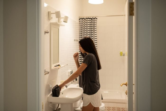 young woman brushing teeth before bed