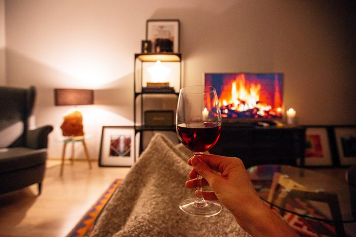 glass of red wine at night while sitting on couch
